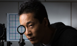 Doctoral student Joseph Choi is pictured with a a multidirectional `perfect paraxial' cloak using 4 lenses.Credit: University of Rochester Newscenter