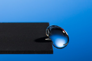 Professor Chunlei Guo has developed a technique that uses lasers to render materials hydrophobic, illustrated in this image of a water droplet bouncing off a treated sample.Photo: J. Adam Fenster / University of Rochester
